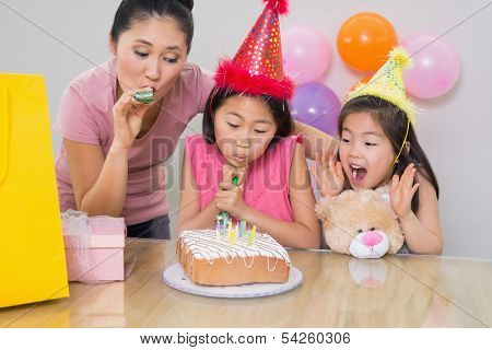Close-up of cute little girls and mother blowing noisemakers at a birthday party
