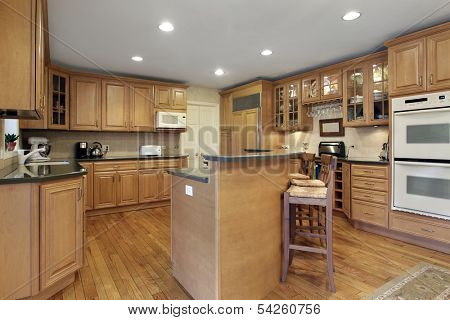 Kitchen with oak cabinetry and double decker island