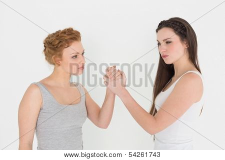 Two serious young female friends arm wrestling against white background