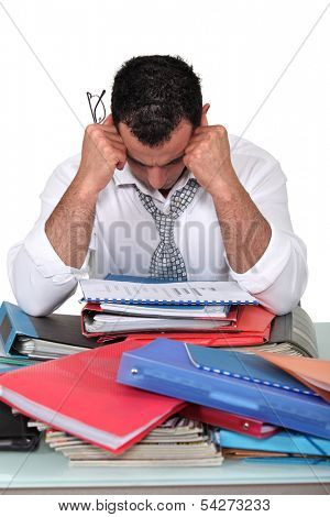 Depressed businessman surrounded with paperwork