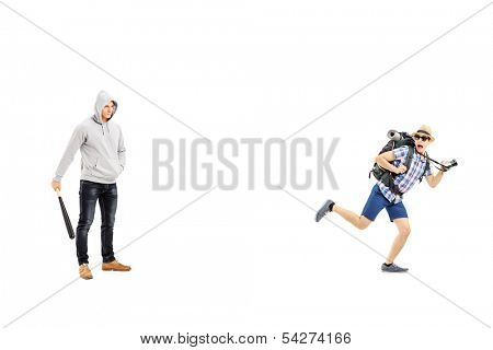 Guy with hood over his head holding a baseball bat and scared tourist trying to run away isolated on white background