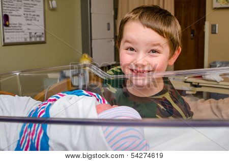 Excited boy meets his infant sibling for the first time after delivery at hospital