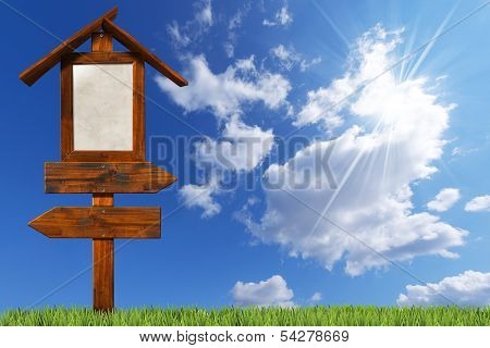 Double Directional Wooden Signs On Blue Sky