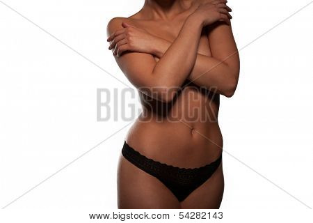 Torso of a beautiful topless woman in panties posing with her arms raised to accentuate the shape of her breasts and nipples, isolated on white