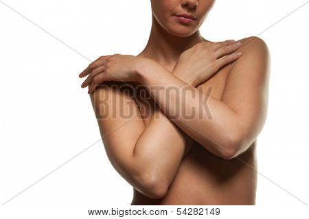 Topless woman posing with her arms across her breasts concealing her nipples as she stands facing the camera, upper torso view isolated on white