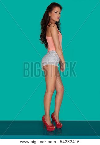 Beautiful woman with long wavy brunette hair standing sideways in skimpy shorts and high heels on a turquoise background