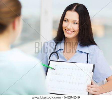 healthcare and medical concept - female doctor or nurse showing cardiogram to patient