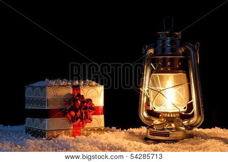 A gift wrapped Christmas present in the snow illuminated by the glow of an oil filled lantern.