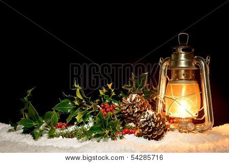 An oil filled lantern sitting in snow with holly, ivy and pine cones illuminated by the glow of the lamp.