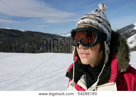 A young skier wearing a pair of goggles on a sunny day