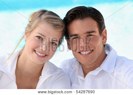 Smiling young couple sitting in the sunshine