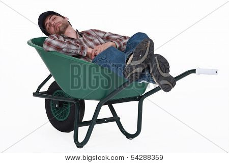Worker taking a nap in wheelbarrow