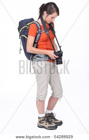 cute female hiker with camera isolated on white