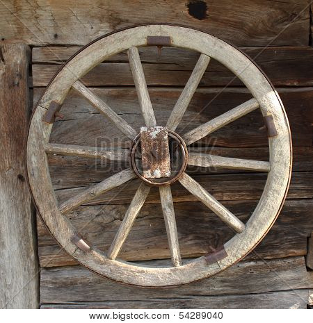 Vintage wooden carriage wheel, wood background