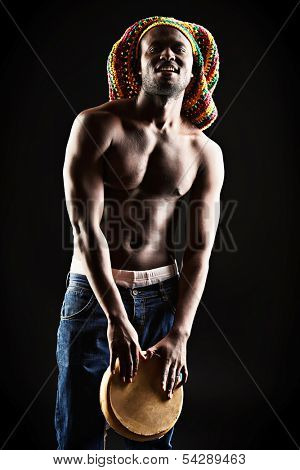 Rastafarian african american man playing his drum. Over dark background.