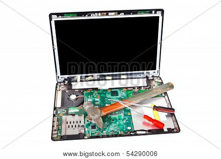 Laptop Disassembled With Hammer And Screwdrivers On It