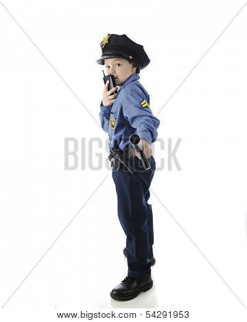 Side view of a young elementary boy looking back at the viewer as he holds out his nightstick and talks on his walkie talkie.  On a white background.