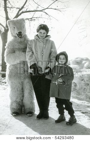VILLARS, FRANCE - CIRCA FEBRUARY 1954: vintage picture of mother and daughter who pose for photo with fake bear, Villars, France, circa February 1954