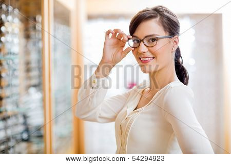 Portrait of beautiful young woman trying new glasses in optician store