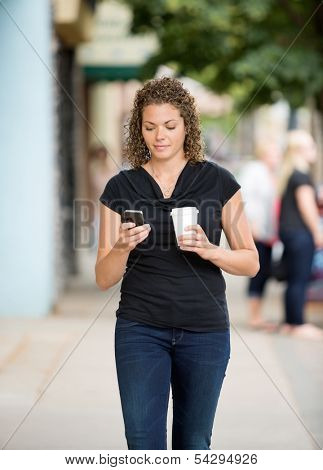 Mid adult woman with disposable coffee cup using smartphone while walking on pavement