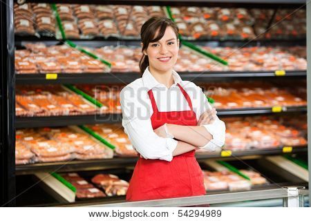 Portrait of beautiful saleswoman standing arms crossed at counter in butcher's shop