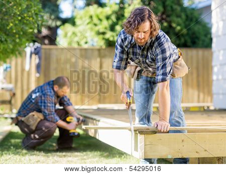 Manual worker cutting wood with saw while coworker drilling in background at construction site