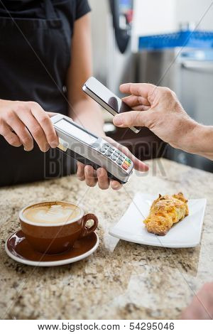 Customer paying for coffee using NFC technology