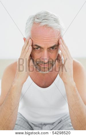 Close-up of a mature man suffering from headache in bed at home