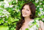 pic of nearly nude  - Portrait of attractive woman near the blossomed tree in the park - JPG