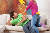 image of couch potato  - Woman trying to clean the hosue and man on a couch - JPG