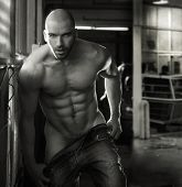 stock photo of undressing  - Erotic portrait of a muscular nude man in industrial garage setting - JPG