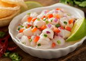 stock photo of peppers  - A freshly made scallop ceviche with red onion cilantro red pepper lime and serrano pepper.