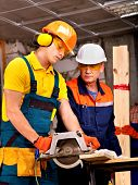 foto of millwright  - Happy group people  builder with circular saw - JPG
