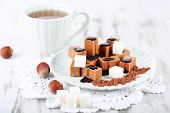 image of toffee  - Many toffee on plate and cup of tea on napkin on wooden table - JPG