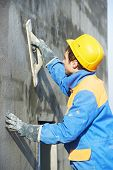 stock photo of putty  - builder at facade plastering work during industrial building with putty knife float - JPG