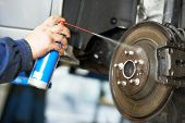 foto of grease  - car mechanic cleaning car wheel brake disk from rust corrosion at automobile repair service station - JPG