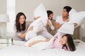 stock photo of pillow-fight  - Cheerful kids and parents  having pillow fight on bed at home - JPG