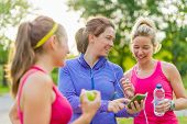 stock photo of adults only  - Group of happy active girls preparing for a run in nature by choosing music on smart phone - JPG