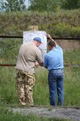 stock photo of shooting-range  - Two men prepare the purpose for shooting - JPG