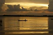 picture of canoe boat man  - People rowing the row boat on golden surface water of river at sunrise clouds reflect on water make a rectangle frame - JPG