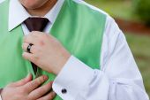 foto of fidget  - A groom is messing with his tie and vest at a wedding reception - JPG