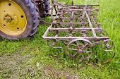 Tractor With Old Agriculture Rake Machinery In Farm