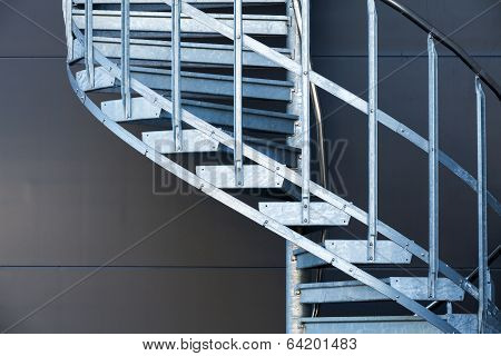 Fragmetn Of Modern Metal Spiral Staircase Above Dark Gray Wall