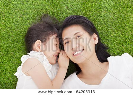 Mother And Daughter Whispering Gossip On The Grass