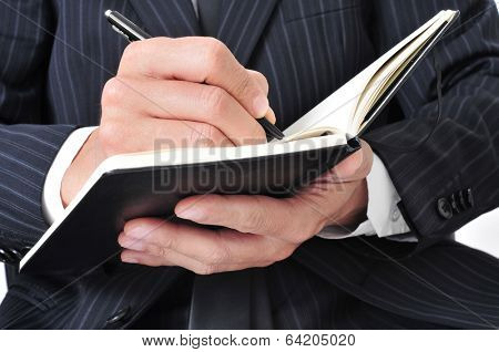 closeup of a businessman writing in a notebook
