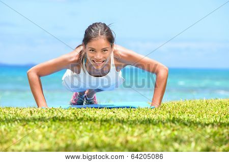 Push-ups fitness woman doing pushups outside on beach on grass. Fit female sport model girl training crossfit outdoors. Mixed race Asian Caucasian athlete in her 20s.