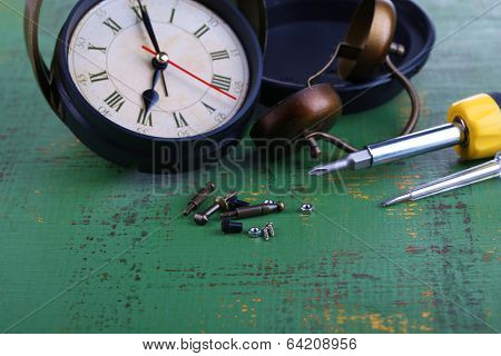 Repair clock on wooden background