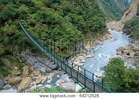 TAIWAN - DECEMBER 28 : A long suspension footbridge crossing the river at Taroko National Park on December 28, 2011 in Hualien County, Taiwan