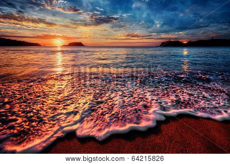 Magnificently colorful ocean sunrise with distant reflections