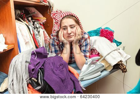 Tired Housewife In Pile Of Not Ironed Clothes